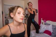 Twee jonge meisjes die op de telefoon in hun ruimte spreken Stock Foto's