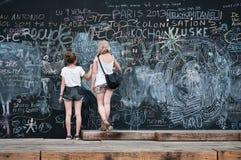 Twee jonge meisjes die op groot bord schrijven Royalty-vrije Stock Foto's