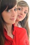 Twee jonge meisjes die op wit worden geïsoleerdf Stock Afbeeldingen