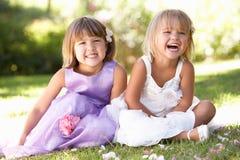 Twee jonge meisjes die in park stellen Stock Afbeelding