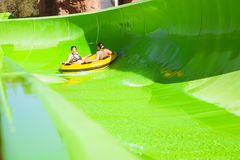 Twee jonge meisjes die pret op vakantie op een dia in waterpark hebben, Stock Afbeelding