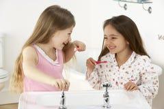 Twee Jonge Meisjes die Tanden borstelen bij Gootsteen royalty-vrije stock afbeelding