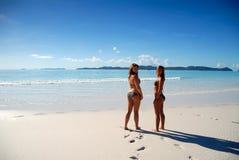 Twee jonge meisjes die zich door paradijsoceaan bevinden Stock Fotografie