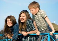 Twee jonge meisjes en jongen het lachen Stock Fotografie
