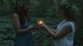 Twee jonge meisjes houden een brandende kaars in het bos stock video