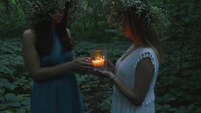Twee jonge meisjes houden een brandende kaars in het bos stock videobeelden