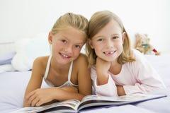 Twee Jonge Meisjes in Hun Pyjama's, die een Boek lezen Stock Afbeeldingen