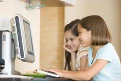 Twee jonge meisjes in keuken met computer het glimlachen royalty-vrije stock foto