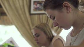 Twee jonge meisjes in koffie bestuderen stock footage