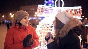 Twee jonge meisjes lopen in de winter door de verfraaide straten van de stad Nieuw jaar, vakantie, sneeuw stock videobeelden