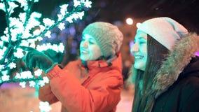 Twee jonge meisjes lopen in de winter door de verfraaide straten van de stad Nieuw jaar, vakantie, sneeuw stock video