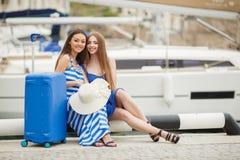 Twee jonge meisjes met een koffer op een Jachthaven Stock Fotografie