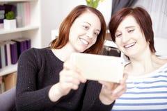Twee jonge meisjes met slimme telefoon Stock Afbeelding