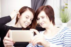 Twee jonge meisjes met slimme telefoon royalty-vrije stock foto