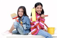 Twee jonge meisjes met verf borstelen en rol Stock Afbeeldingen