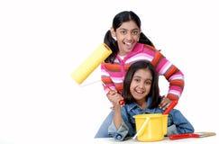 Twee jonge meisjes met verfborstel en rol Royalty-vrije Stock Afbeelding
