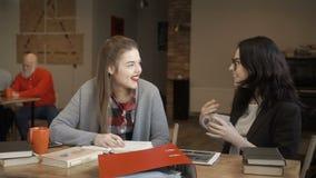 Twee jonge meisjes spreekt terwijl het hebben van onderbreking tijdens het voorbereidingen treffen aan examens bij universiteit stock footage