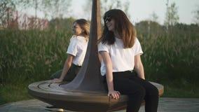 Twee jonge meisjes in t-shirts en zonnebril die op bank in park spinnen stock videobeelden