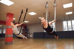 Twee jonge meisjes vliegen yoga en rek in de studio Stock Foto