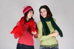 Twee jonge meisjes in warme sjaals en hoeden stock afbeelding