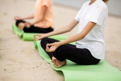 Twee jonge meisjes zitten in de lotusbloemposities inzake yogamatten op zandig strand op een warme dag royalty-vrije stock foto's