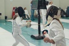 Twee jonge meisjesschermers die het schermen duel op toernooien hebben royalty-vrije stock fotografie