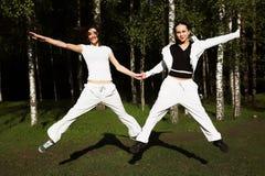 Twee jonge meisjessprong in park Stock Afbeeldingen