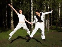 Twee jonge meisjessprong in park Stock Foto's