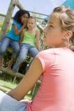Twee jonge meisjesvrienden bij speelplaats het fluisteren Royalty-vrije Stock Foto's