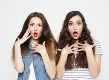 Twee jonge meisjesvrienden die pret hebben Allebei die verraste gezichten maken royalty-vrije stock afbeelding