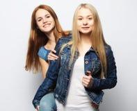 Twee jonge meisjesvrienden die zich en pret verenigen hebben Stock Foto