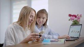 Twee jonge meisjesvrienden kopen schoenen in online winkel, betaalt één vrouw door kreditkaart gebruikend toepassing op haar stock videobeelden