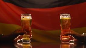 Twee jonge mensen die bierglazen houden tegen Duitse vlag op achtergrond, festival stock videobeelden