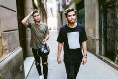 Twee jonge mensen die in de straat lopen stock foto