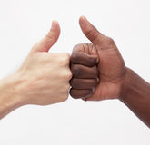 Twee jonge mensen die elkaar de duimen geven ondertekenen omhoog, close-up, studioschot Stock Foto's