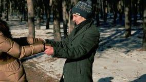 Twee jonge mensen die in het hout in de sneeuw lachen stock footage