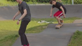 Twee jonge mensen die in het park op speciale golvende weg met een skateboard rijden stock video