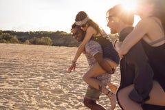 Twee jonge mensen die hun meisjes geven vervoeren per kangoeroewagen ritten Royalty-vrije Stock Afbeelding