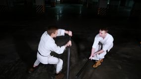 Twee jonge mensen die in kimono hun vaardigheden op een parkeerterrein opleiden Zwaardstrijd stock videobeelden