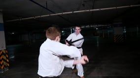 Twee jonge mensen die in kimono hun vaardigheden in vechtsporten opleiden Zwaardstrijd stock videobeelden
