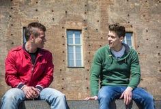 Twee jonge mensen die terwijl het zitten op rand spreken royalty-vrije stock foto