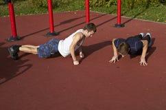 Twee jonge mensen doen opdrukoefeningen van de grond. Stock Afbeeldingen