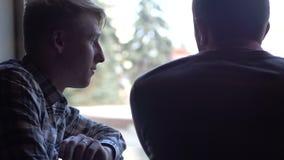 Twee jonge mensen in een koffie die een project bespreken stock footage
