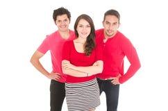 Twee jonge mensen en een jong meisje kleedden zich in rood Stock Afbeelding