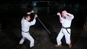 Twee jonge mensen in kimono opleiding op een parkeerterrein Zwaardstrijd stock video