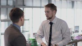 Twee jonge mensen zijn het spreken, zich bevindt in autosalon, bedrijfsmensen die belast met dialoog over het werk, op achtergron stock video