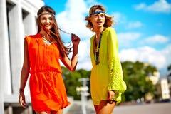 Twee jonge modellen van hippievrouwen in heldere kleurrijke hipsterkleren stock fotografie
