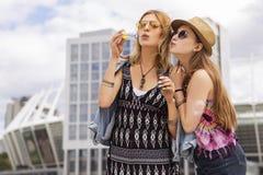 Twee jonge mooie blonde hipster meisjes op de zomerdag die fu hebben stock afbeeldingen
