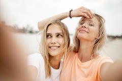 Twee jonge mooie blondemeisjes nemen een selfie op het strand op een warme winderige dag royalty-vrije stock fotografie