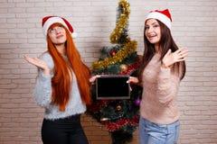 Twee jonge mooie glimlachende meisjes die in Kerstmankappen een tablet houden stock afbeelding